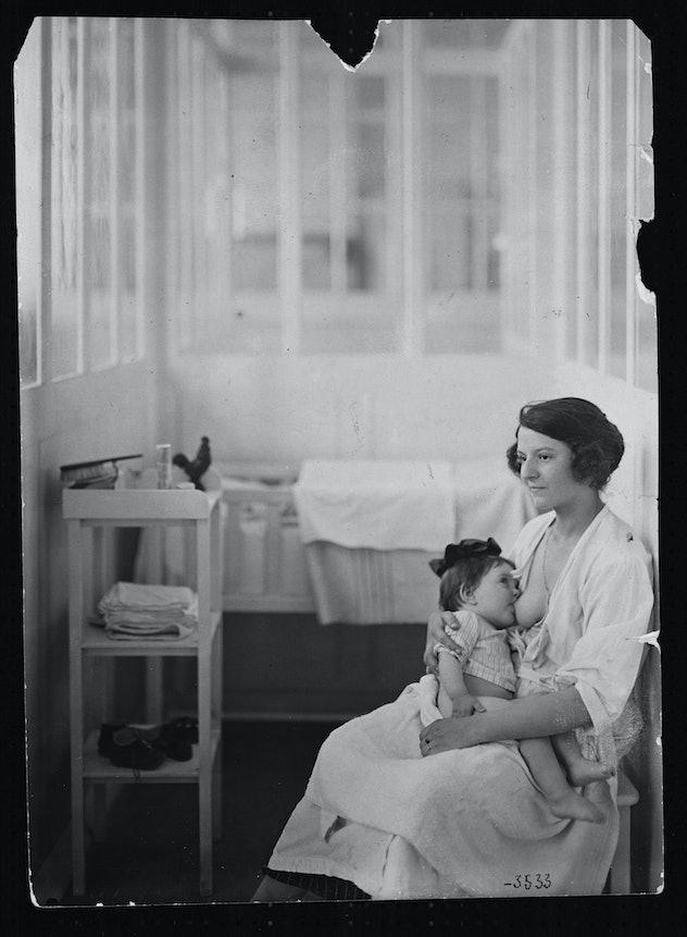 woman nursing baby in hospital nursery in 1930s