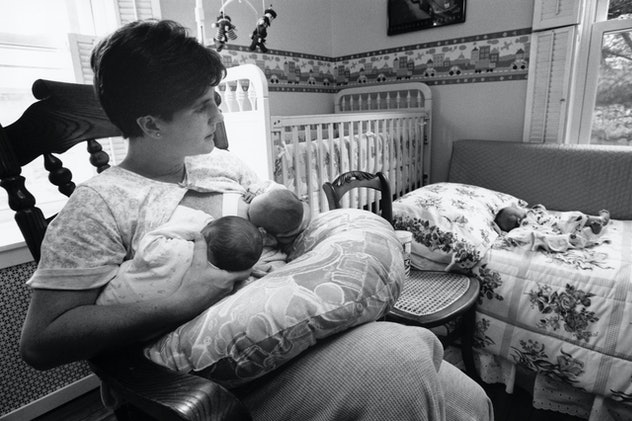 Woman who gave birth to triplets tandem breastfeeding two babies in rocking chair, while one sleeps ...
