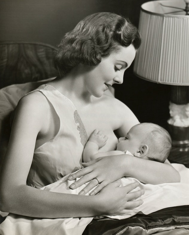 vintage breastfeeding photo of woman breastfeeding baby propped on pillows