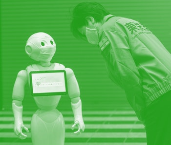 A robot known as Pepper by SoftBank Robotics Europe can be seen carrying a screen on its front and observing a pedestrian with a mask on.
