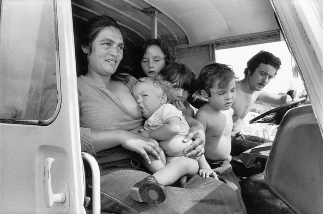family traveling inside a van with four children in 1980s, mom in passenger seat nursing baby