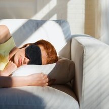 A woman with her eyes covered naps on a couch. The FDA approved Esketamine nasal spray for treatment-resistant depression and suicidal ideation.