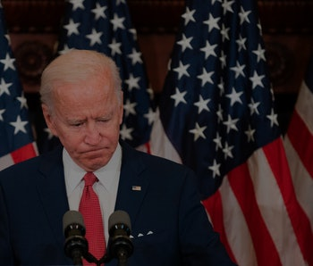Former vice president Joe Biden can be seen looking down while standing at the podium. Behind Biden, there is the United States flag.