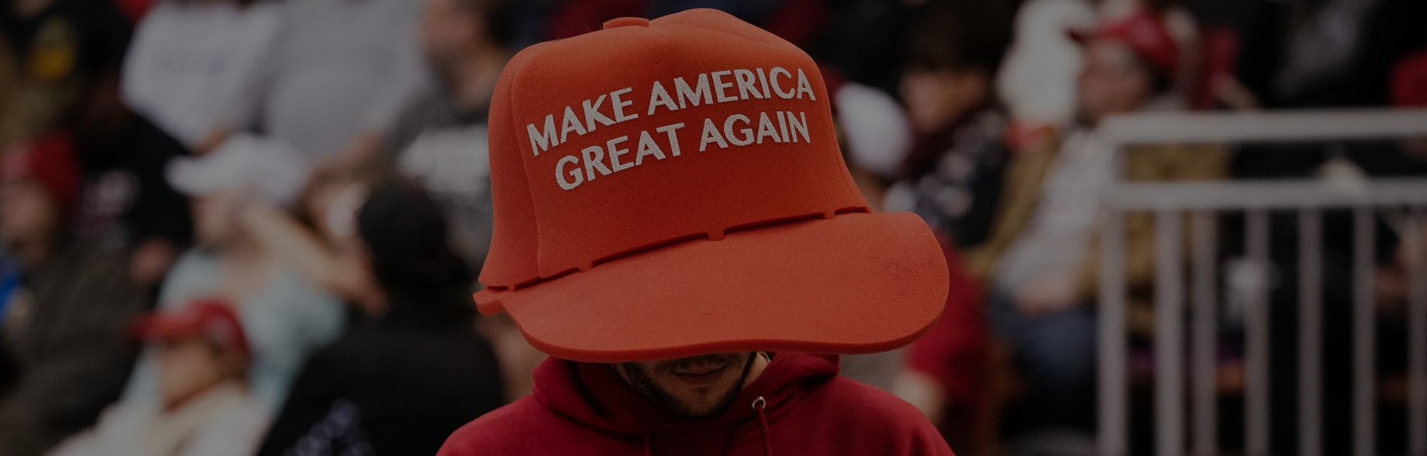 """A Trump supporter can be seen wearing a large sized hat with """"Make America Great Again"""" on it. His shirt says the same statement. They are both red in color. He is holding a phone in both hands."""