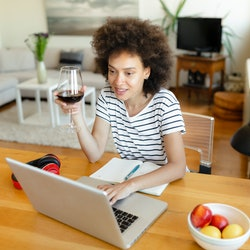 A woman drinks wine at her laptop. These doctor-recommended ways to improve your memory can help you stop forgetting things.