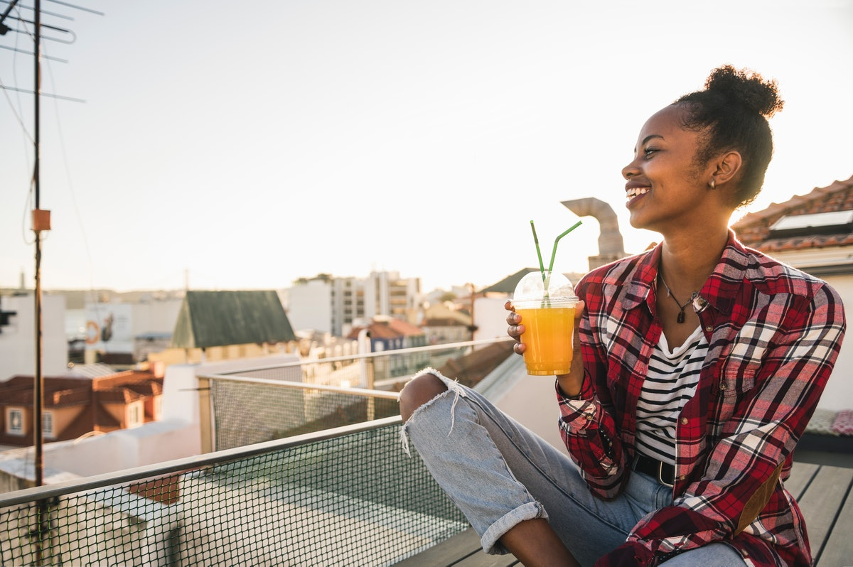 A happy woman watches the sunset from her balcony, while drinking a tea.