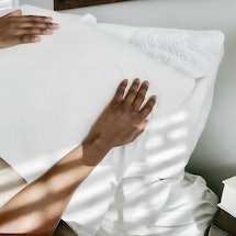 A woman with a pillow over her face tries to sleep. Women explain their quarantine sleep hacks.