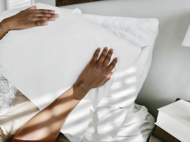 A woman with a pillow over her face tries to sleep. Women explain their quarantine sleep hacks.