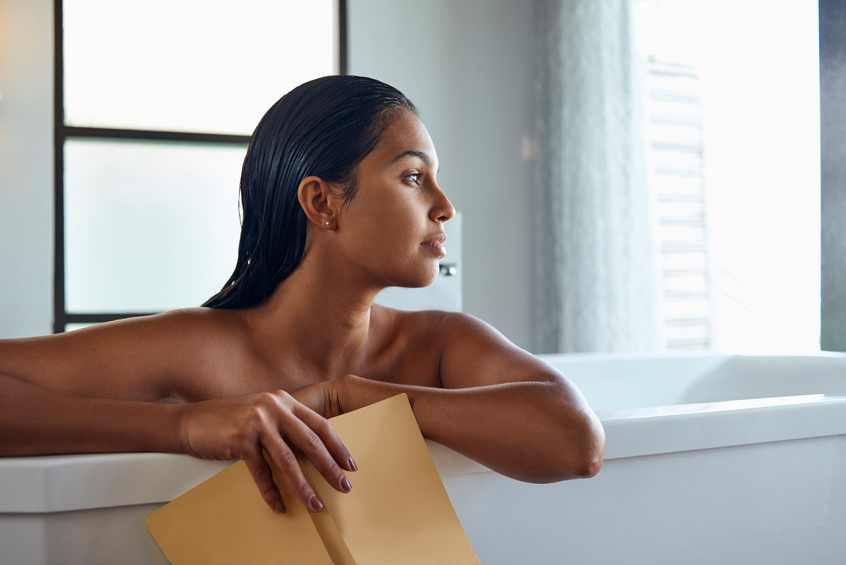 A woman takes a bath with a book. A soothing bath can help before sleep.