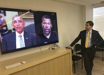 The former United States president Barack Obama is seen on a screen next to another screen showing comedian Jordan Peele. A man is observing the video which depicts the comedian impersonating Obama's voice for a deepfake.