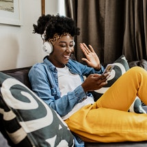 A woman sits on a couch looking at her phone. These are the differences between instagram reels vs. triller.