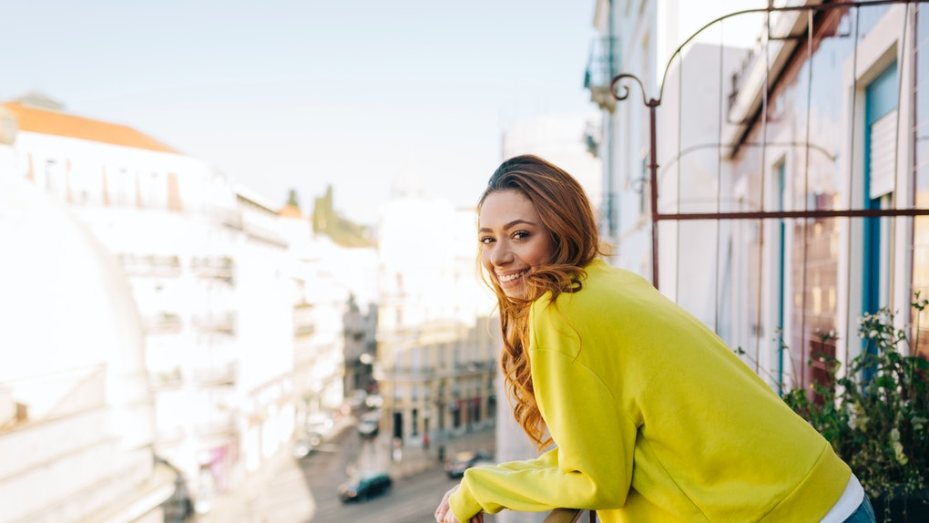 A happy woman in a yellow sweater, enjoys the views from her balcony.