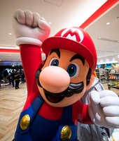 A large Mario statue can be seen with the Super Mario Brothers character throwing a fist in the air.