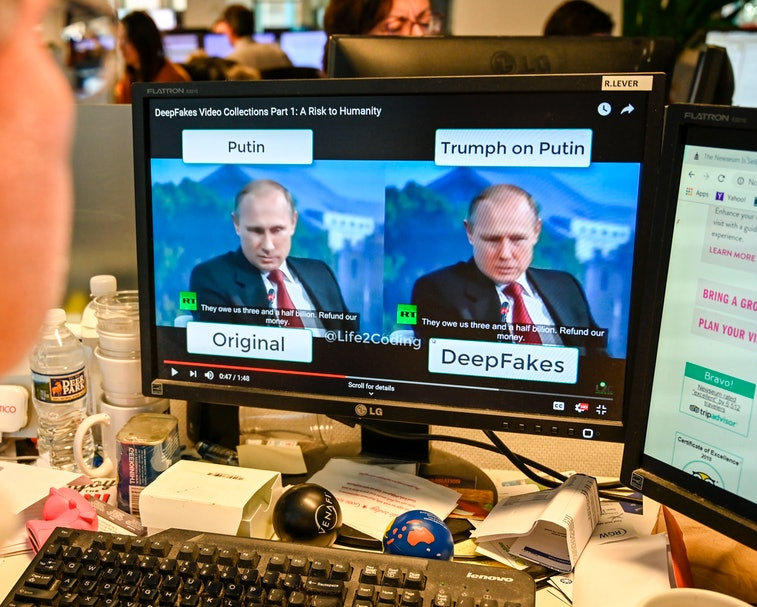 """Russian leader Vladimir Putin is seen on two screens. The title above one screen reads """"Putin"""" and it is the original image. The second screen's title os """"Trumph on Putin"""" and the bottom text reads """"DeepFakes."""" There is a keyboard in front of the screen alongside other accessories."""