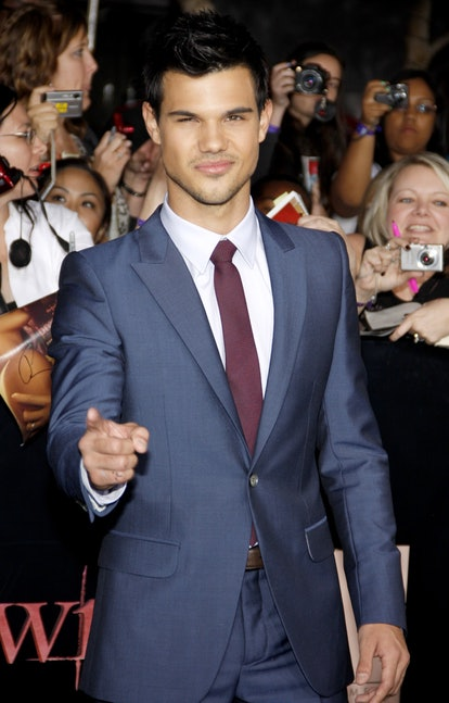 Taylor Lautner stands before a group of 'Twilight' fans, pointing at the camera. He wears a blue suit with a white shirt and a burgundy tie.
