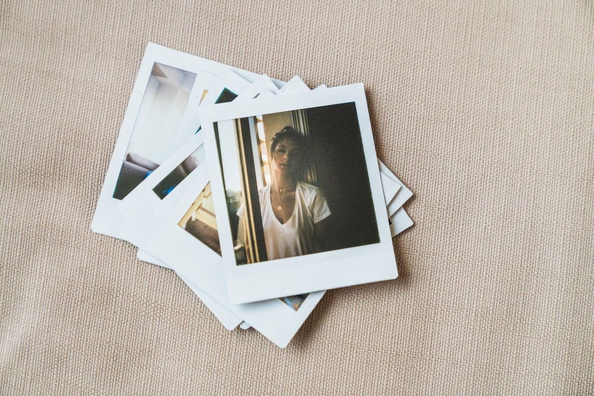 A stack of Polaroid pictures shows a girl standing in a sunny window on top.