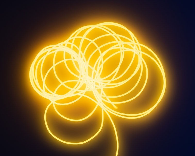 A fluorescent wire can be seen in bright yellow color. It's made up of multiple spirals with its tail end heading downward. The background is black.