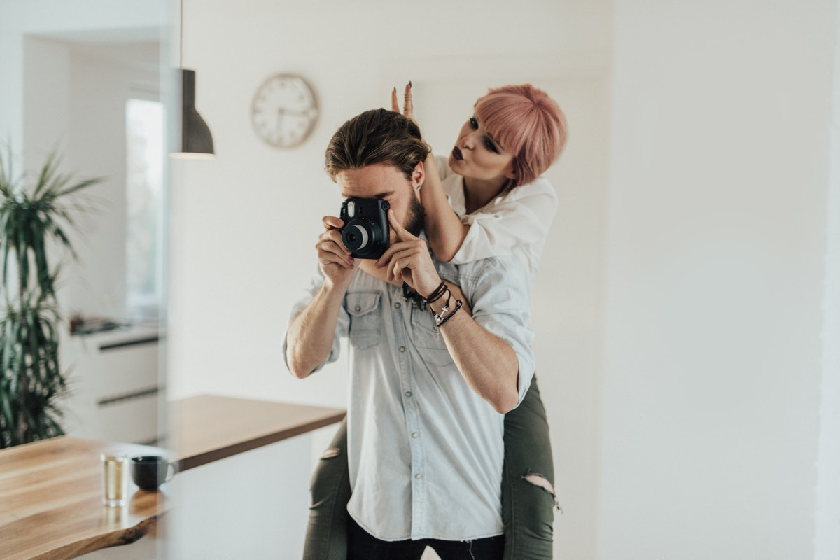 A young couple takes a mirror selfie on their digital camera in a minimalistic home.