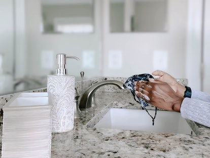 A woman washes a face mask in a sink. Long haul covid symptoms include brain fog and heart rate issues, according to one patient.