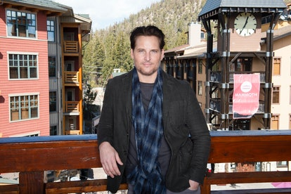 Peter Facinelli stands on a balcony in front of a pink apartment building. He wears a grey shirt and jacket with a blue plaid scarf.