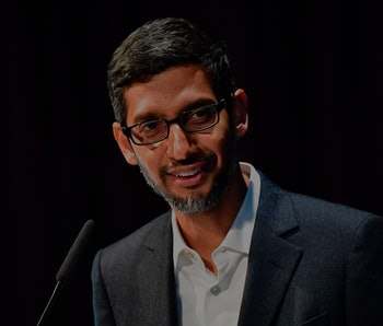 Google CEO Sundar Pichai can be seen talking to an audience. The background behind Pichai is black. He is wearing eyeglasses, a white shirt, and a dark gray coat.