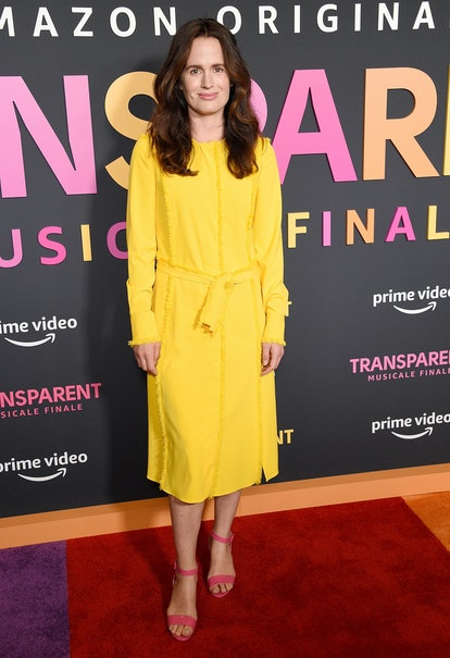 Elizabeth Reaser stands on the red carpet, smiling. She is wearing a yellow dress and a pair of pink sandals.