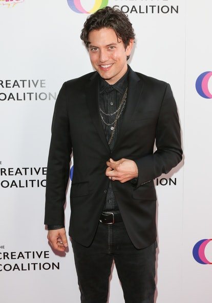 Jackson Rathbone stands on the red carpet, smiling. He wears a black suit, a black pinstripe shirt, and several chain necklaces.