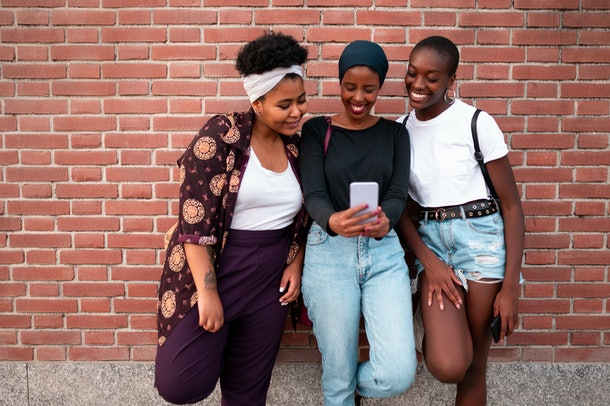 Three happy best friends lean against a brick wall, while looking at a phone.