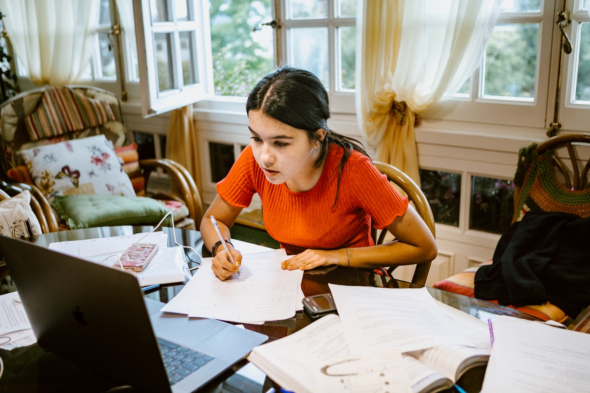 A young woman studies at a kitchen table with her laptop and papers spread all over.