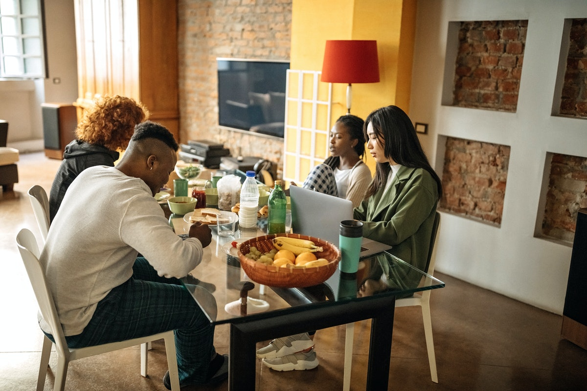 A group of students hangs out at a kitchen table in a college collab house, with food and their laptops.