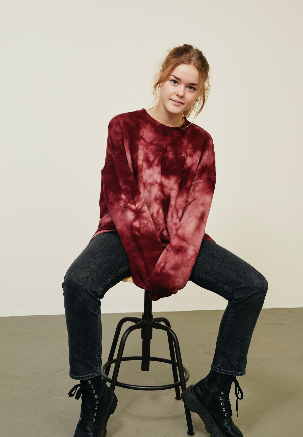 A young woman poses on a stool while wearing a tie-dye crewneck sweatshirt, black jeans, and combat boots for fall.