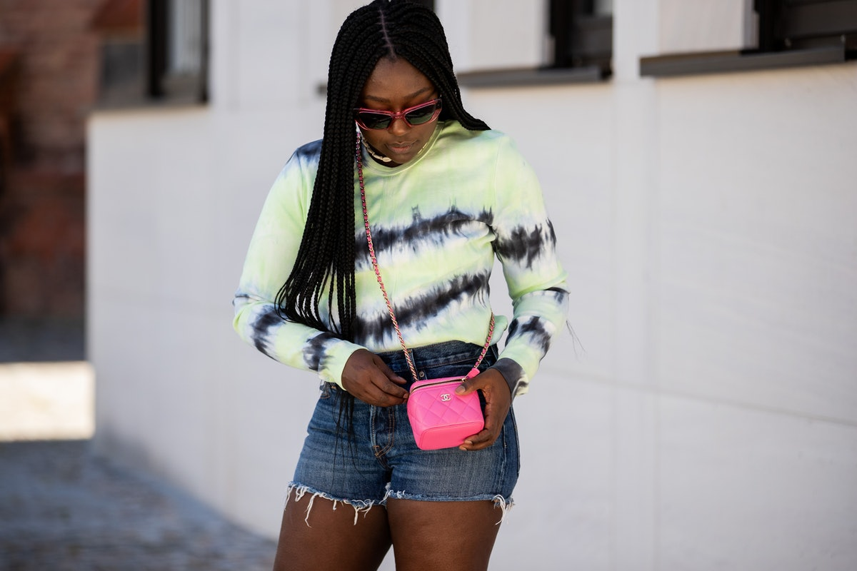 A young Black woman poses in the street while wearing a long-sleeve tie-dye shirt and a hot pink Chanel bag.