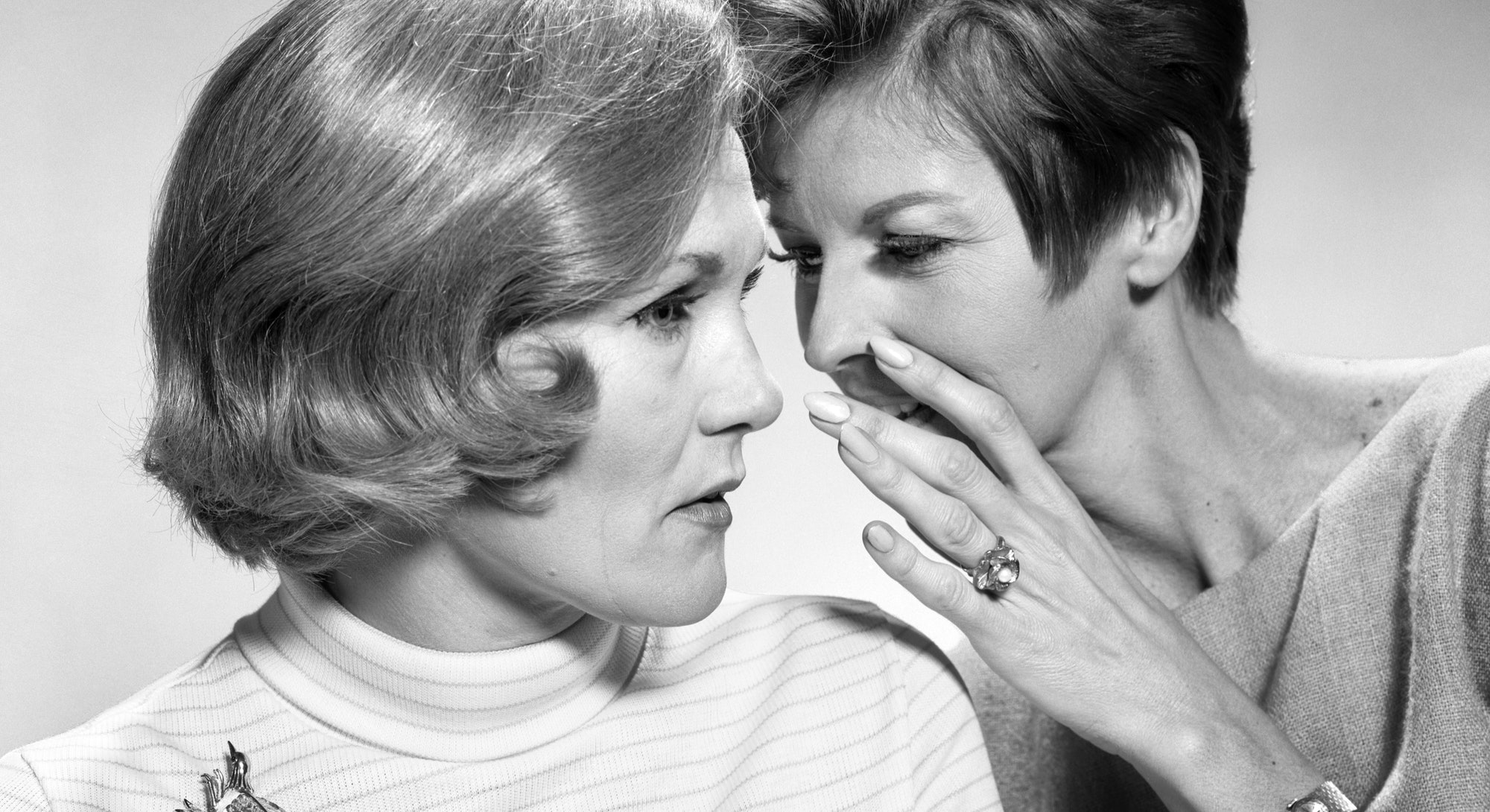 A woman tells her friend a secret. Researchers told the Atlantic that talking quietly could lower covid-19 transmission risk.