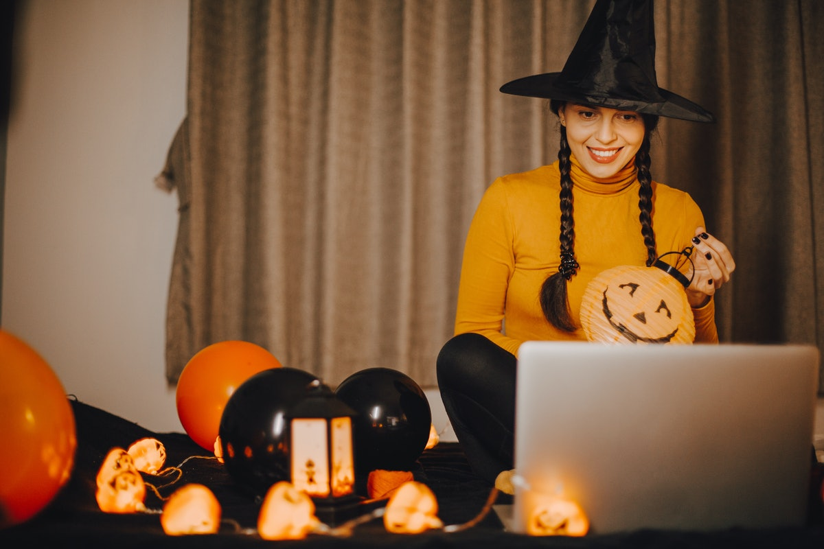 A woman dressed like a witch sits in front of her computer for a virtual Halloween party at home.