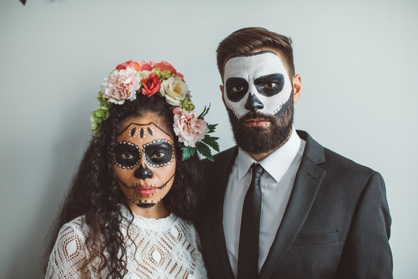 A young couple poses for a Halloween photo while wearing face paint and standing against a blank wall in their home.