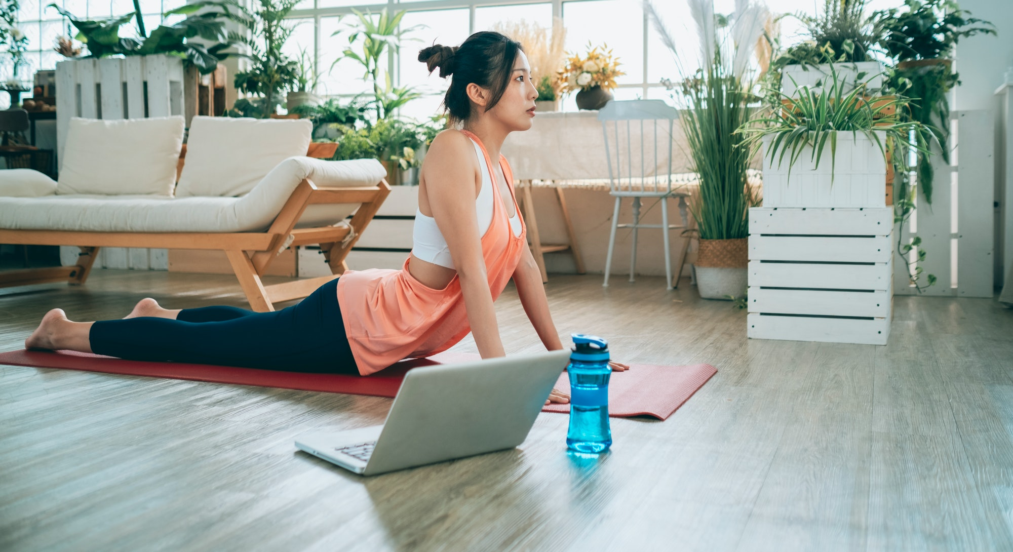 woman doing yoga in front of her laptop