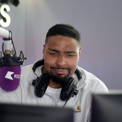 Jordan banjo pictured in the Kiss radio studio with headphones around his neck and a hurt expression on his face