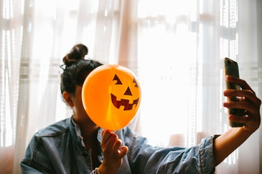 A young woman poses with a pumpkin balloon in front of her face while holding up her phone.