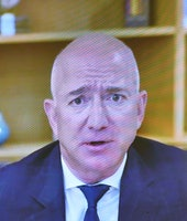 Jeff Bezos is seen in a suit and tie on a TV screen. He appears to be perspiring as his nearly hairless head shines under the fluorescent light.