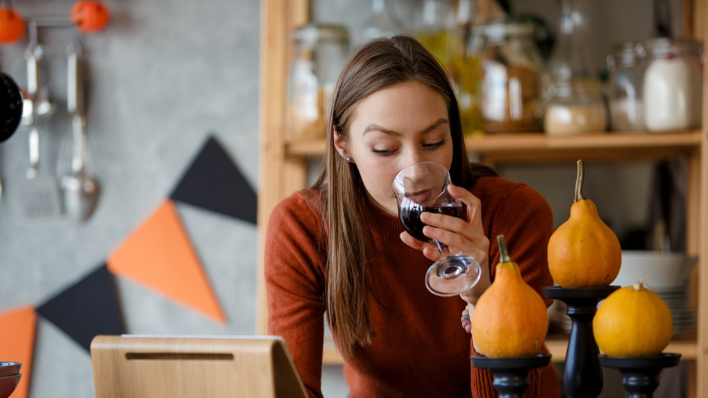 A woman sips a glass of red while in her kitchen that's decorated for Halloween while looking at her tablet.