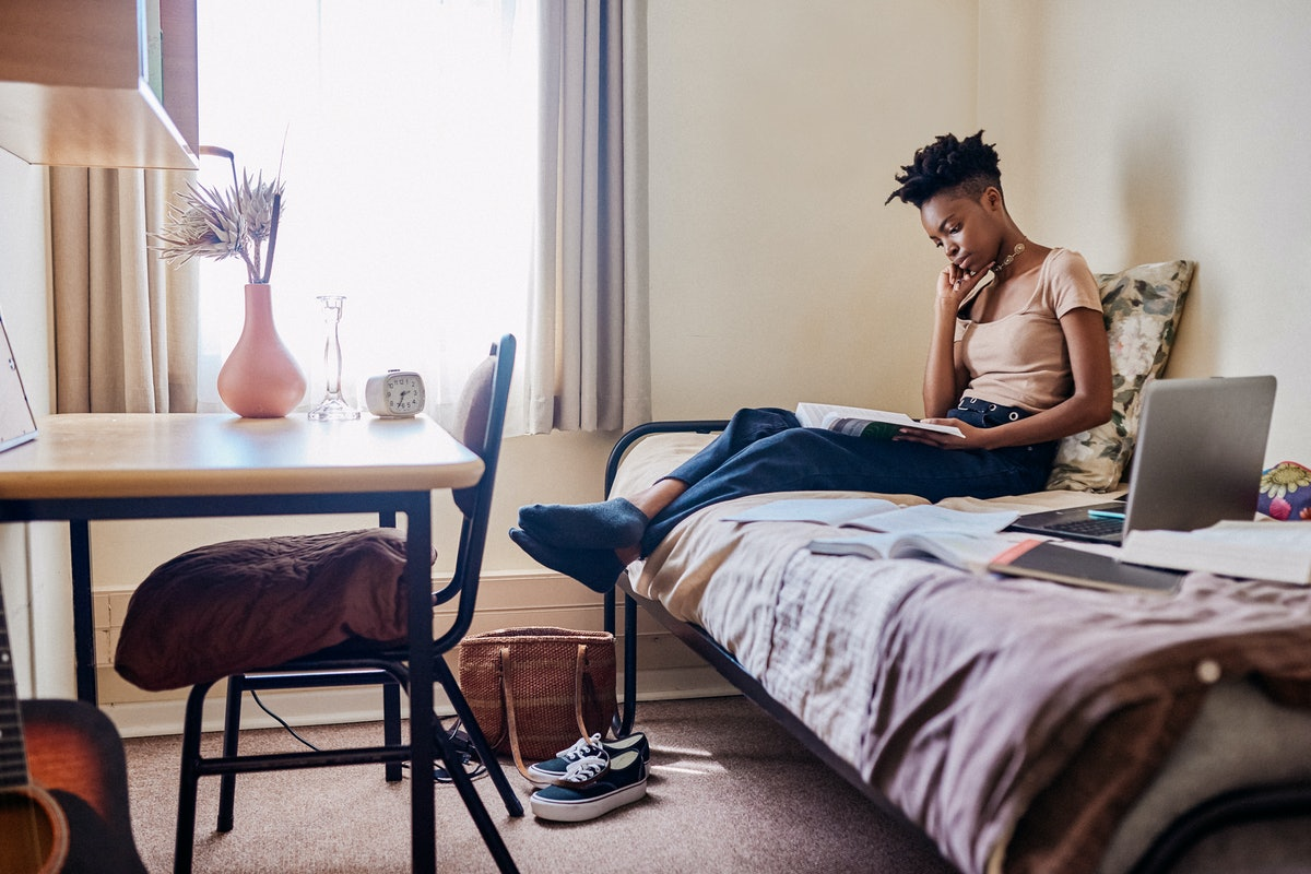 A woman reads a textbook and studies on her bed in her college dorm room.