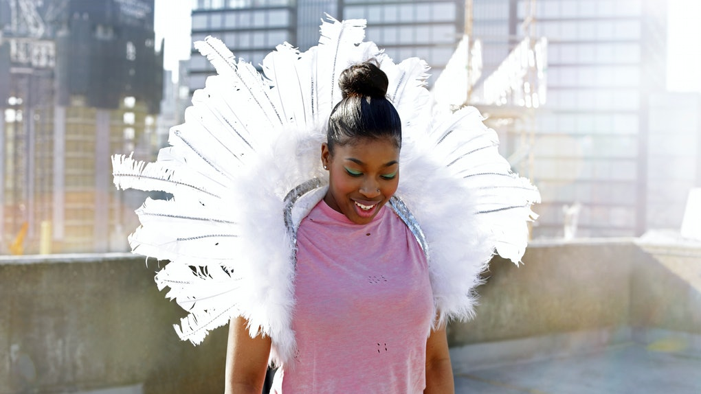 A happy woman wearing a pink T-shirt, angel wings, and a top knot smiles on a rooftop on a sunny day.