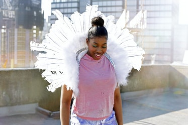 A happy woman wearing a pink T-shirt, angel wings, and a top knot smiles on a rooftop on a sunny day...