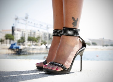 Feet in high heels with a Playboy bunny logo tattoo.