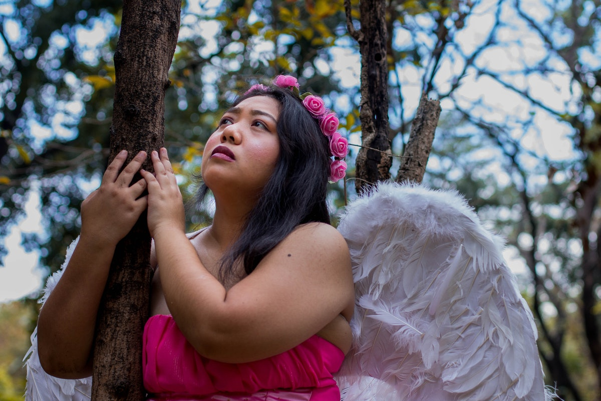A woman in a flower crown and angel wings hugs a tree while looking up at the sky in the woods.