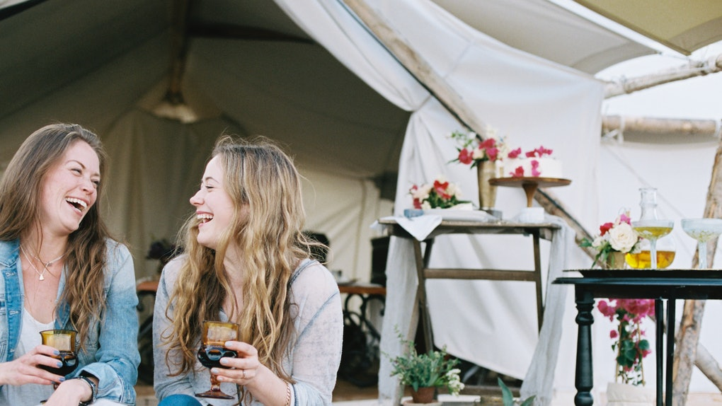 Two friends glamping in the backyard hold wine glasses and laugh.