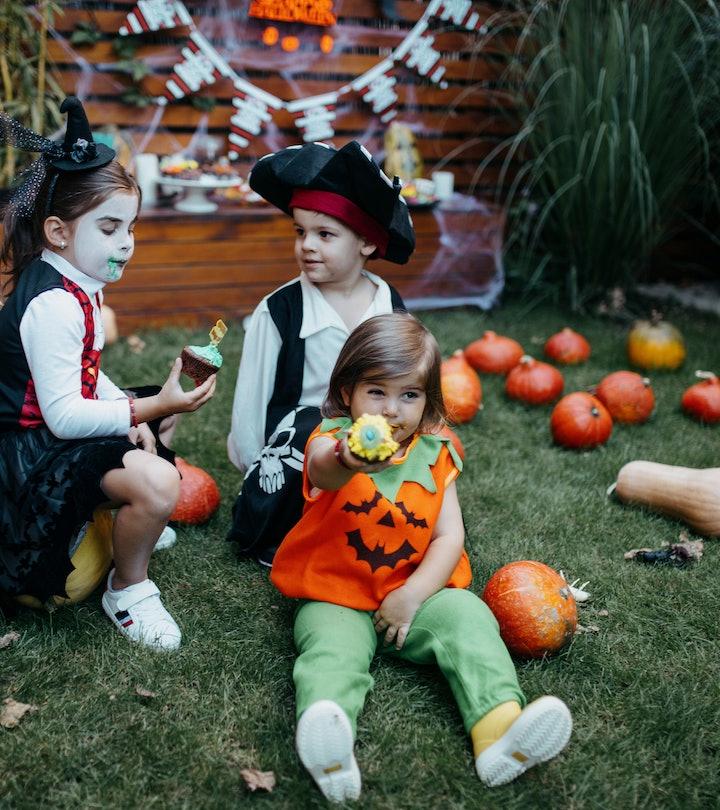 kids in halloween costumes sitting in backyard