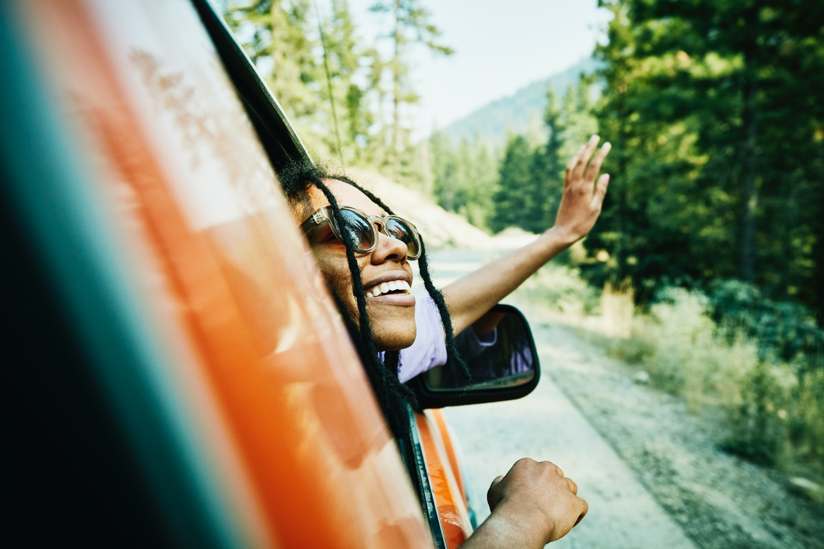 A happy woman with sunglasses on smiles out the window on a road trip.