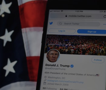 Trump's Twitter account displayed on an iPhone with a US flag in the background.