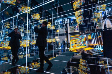 A man standing in a mirrored room of TVs.